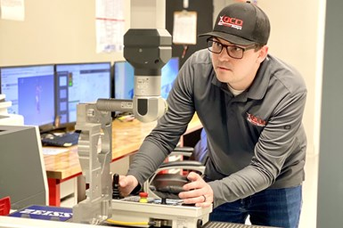 An employee at Olson Custom Designs conducts a part quality check on a coordinate measuring machine.