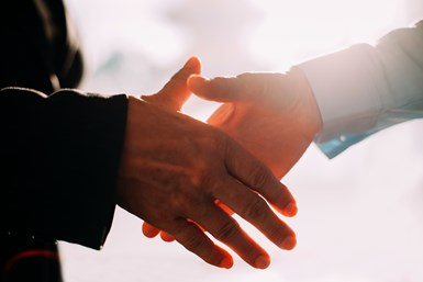 A stock photo of two people in business attire shaking hands