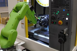 Man programs a cobot in front of a machine tool