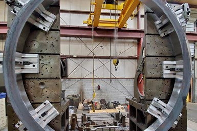 A partial photo of the ring, with special attention to the six workholding plates and accompanying clamps