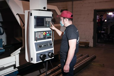 A photo of a TPEI machinist using the Romi C 830's Siemens control