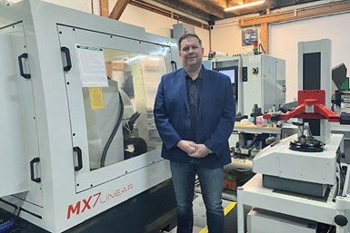 A photo of Taylor Toolworks president Jesse Taylor standing in front of his shop's Anca MX7 Linear tool grinder