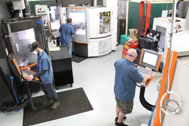 An image of three Westminster Tool machinists working in the shop's new, centralized milling cell
