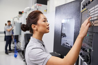 A stock photo of a woman operating a CNC machine