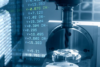 A stock photo of a CNC device with code projected next to it