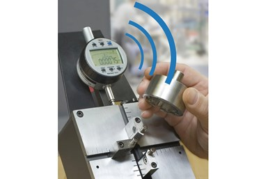 A photo of a person holding a piece near a digital indicator, with digitally added blue curves drawing attention to the digital dial.