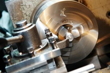 车床车削工件的照片,切削工具向工件延伸。
