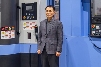 A photo of James Kim, new CEO of Doosan Machine Tools America, in front of a Doosan machine