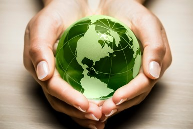 A stock photo of a person cupping a green globe in both hands