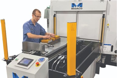 A partial press photo showing a machine shop employee placing items on Midaco's automatic pallet changer with a hydraulic docking system