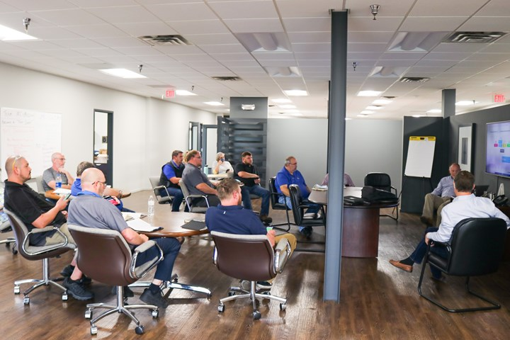 A photo of Mark Beck and Tony Butler leading a collaborative meeting between KAM Tool & Die and JMC Tool & Machine leadership