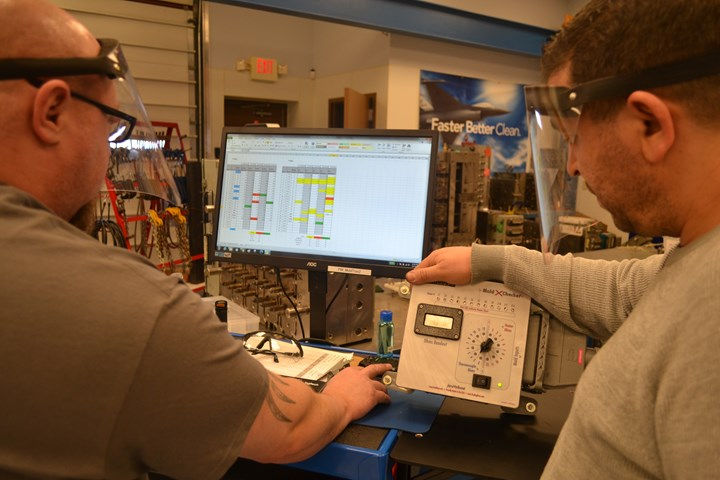 Two workers viewing maintenance data.