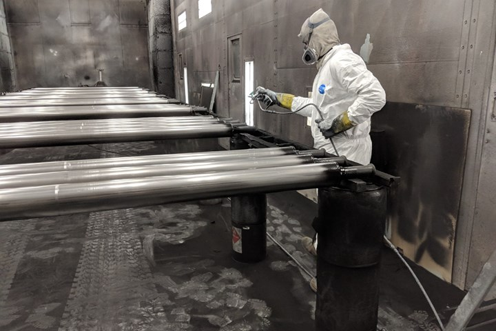 A Kaser employee carrying out a liquid coating process