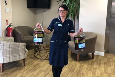 A photo of a hospice worker posing with two paint buckets filled with HMG hand sanitizer