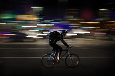 A stock photo of a man riding a bike through an urban environment at night