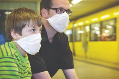 A stock photo of a man and a boy wearing masks in a hospital environment