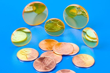 A photo of the new Laser Research Economy CO2 Engraving Lenses focusing on pennies