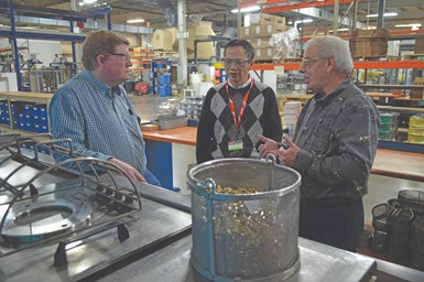 men talking at vacuum vapor degreasing unit at Electro-Spec Inc.