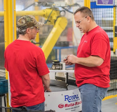 two operators on shop floor discussing part