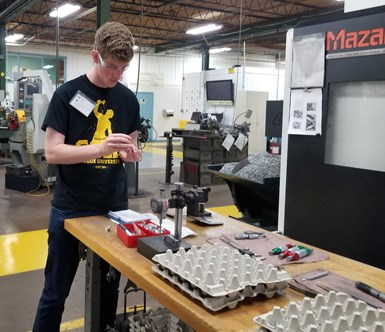 intern working on parts on the shop floor next to Mazak machine tool
