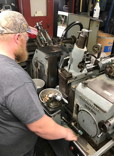 operator working on in-feed grinder