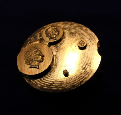 micromachined portraits of the queen on brass