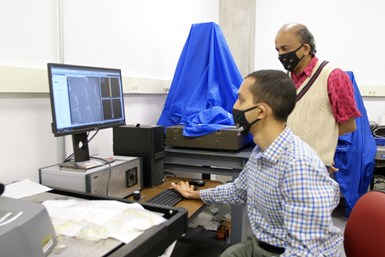 Purdue University engineers Anirudh Udupa (seated) and Srinivasan Chandrasekar (standing) analyze metal surfaces to look for deformations created during cutting to determine how applied materials affect the quality of the cut. (Purdue University image/Erin Easterling)