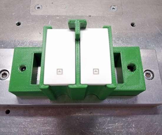 Herramienta de la línea de montaje impresa en 3D, con impresora deStratasys, ydiseñada para sujetar los interruptores durante el proceso de producción.
