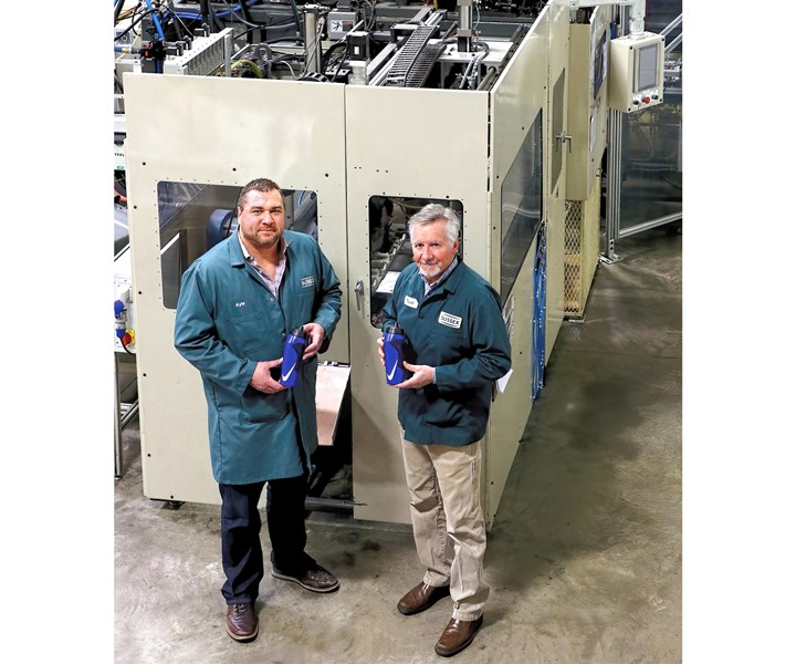 Sussex IM CEO Keith Everson (right) and Kyle Kopp, v.p. of manufacturing, in front of the trimming and leak-testing station of the automated injection and blow molding cell that produces sports water bottles with IML.