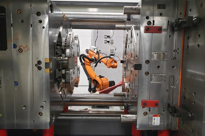 Six-axis robot delivers inserts and removed finished parts from the two-shot mold