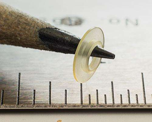 A small part, machined from plastic, is balanced on a pencil tip.