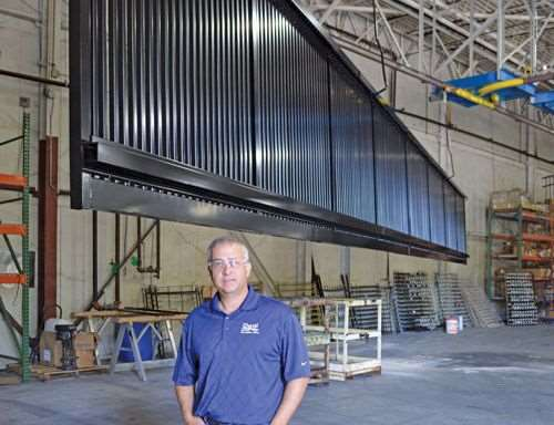 Co-owner Doug Brady stands underneath a 53-foot section of fence that iDeal Aluminum Products manufactures and powder coats.