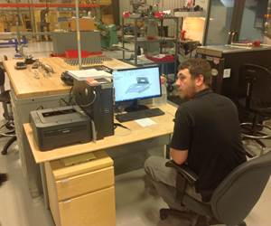 TMI Autotech employee looks over part drawing