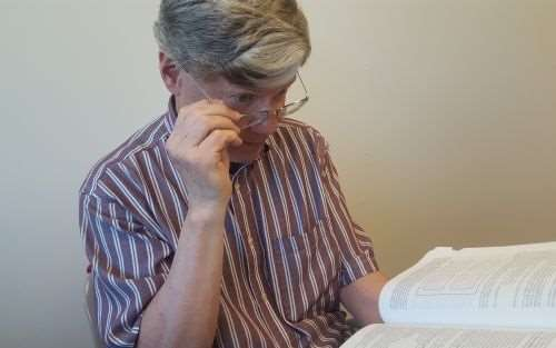 """Editor-in-Chief Mark Albert peers over his glasses at the large print of """"Machinery's Handbook"""""""