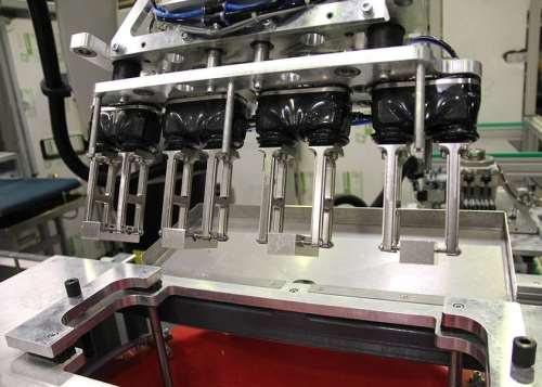 Automated finishing process that uses one or more robots to immerse the workpieces into the agitated media.