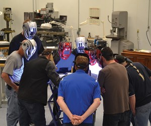 A circle of employees gather around while a technician performs work.
