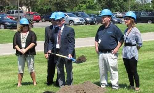 The honor of moving the first shovelful of earth at Hydrotech's groundbreaking belonged to company president, Pete Jones, as other company executives stand beside him.